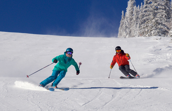 Couple skiing close togehter down a groomed trail.