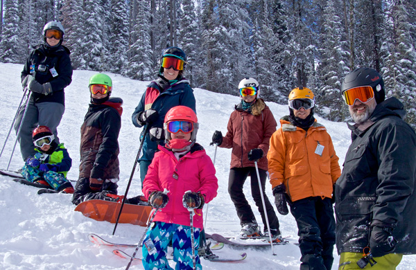 Group of adults and kids skiing on the mountain.