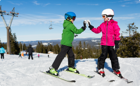 Two young skiiers high-fiving next to a chairlift.