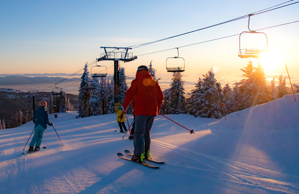 Father and his kids skiing on the mountain at sunset.