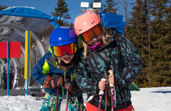 Two young female skiiers smiling.
