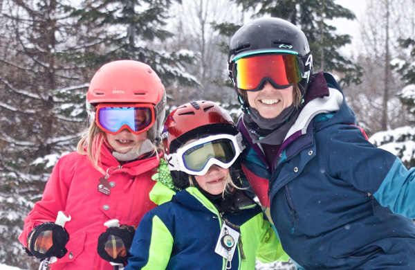 Woman and two kids smiling.