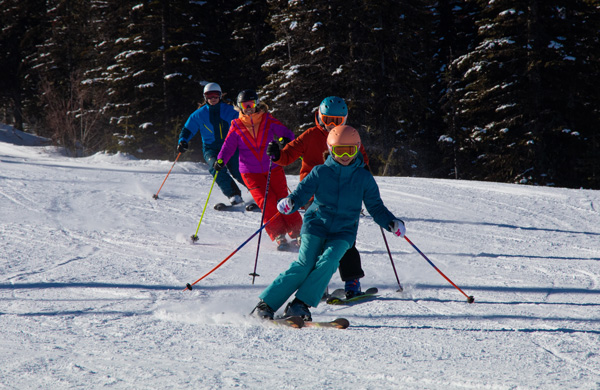 Group of young kids skiing with their parents.