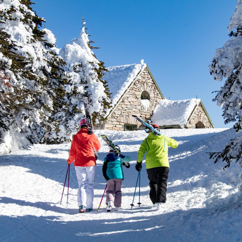 Family of skiers walking up to the summit lodge at Mount Spokane.